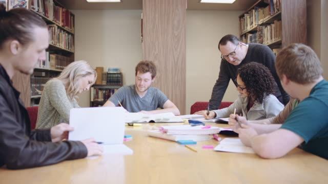 vídeos de stock, filmes e b-roll de mais velho professor masculino auxiliando um grupo de estudantes em uma biblioteca - aluno mais velho