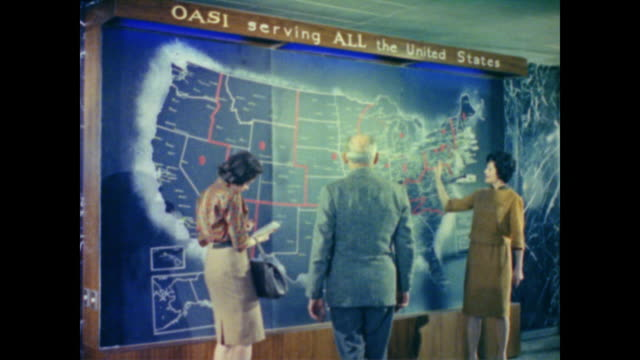 1962 older man and younger woman enjoy tour of social security office - explaining stock videos & royalty-free footage