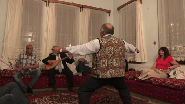 Older man dancing while others play instruments