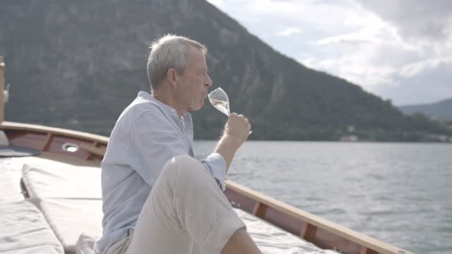 older man enjoying champagne on a boat on a lake - one senior man only stock videos & royalty-free footage