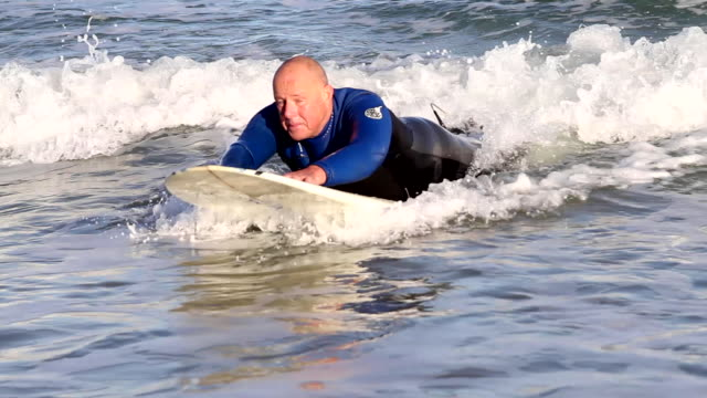 older man gliding through waves lying on a surfboard
