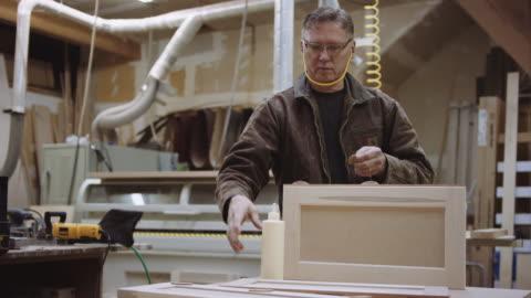 older man glueing items to wood piece - sander stock videos & royalty-free footage