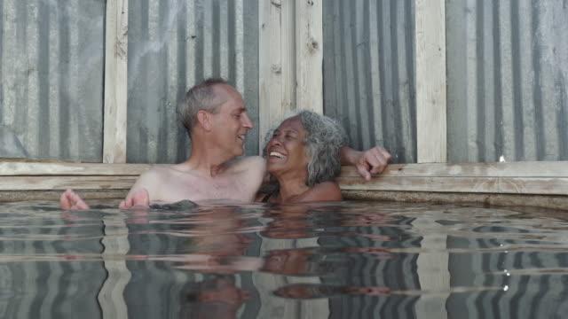 vídeos de stock, filmes e b-roll de 4k uhd: homem mais velho pega um beijo de sua esposa durante a imersão em uma primavera quente - health farm