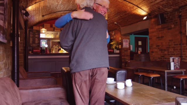 older man greeting friend in bar - modern manhood stock videos & royalty-free footage