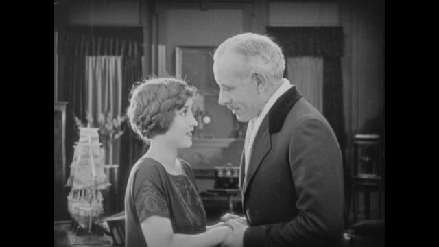 1925 older man hold hands with young woman until he leaves - silent film stock videos & royalty-free footage