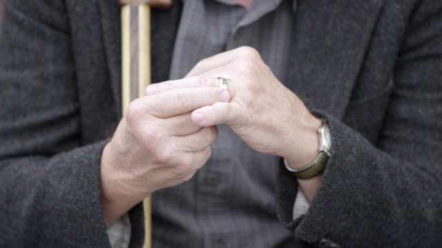 older man holding wedding ring on his fingers - ehering stock-videos und b-roll-filmmaterial