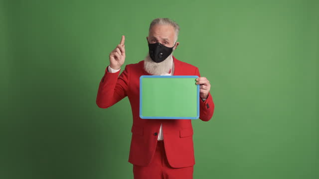 older man  in protective face mask shows  green poster and shows raised finger - shirt and tie stock videos & royalty-free footage