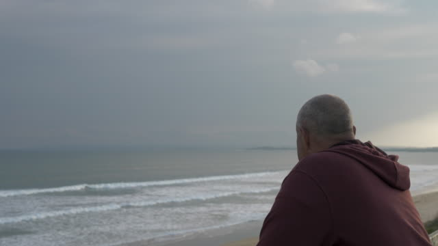 older man looking at the ocean