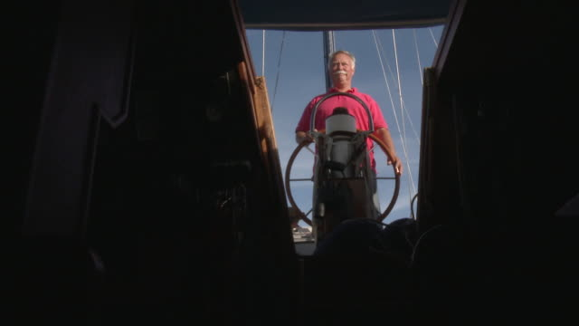 MS Older man looking out to sea from behind steering wheel of his sail boat / Wismar, Mecklenburg-Vorpommern, Germany