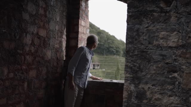 älterer mann schaut durch eine schlossmaueröffnung - schlossgebäude stock-videos und b-roll-filmmaterial