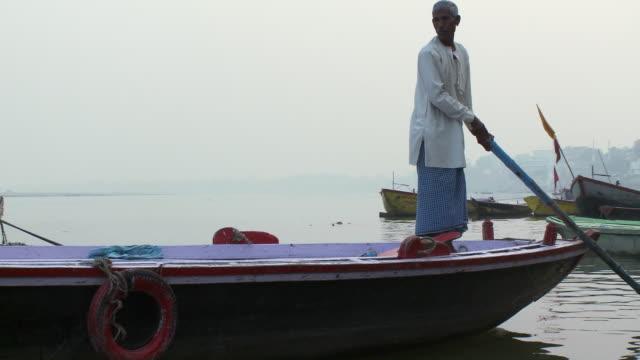 older man on a boat navigating by the wharf. - 年配の男性一人点の映像素材/bロール