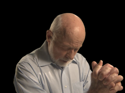 older man praying - this clip has an embedded alpha-channel - pre matted stock-videos und b-roll-filmmaterial