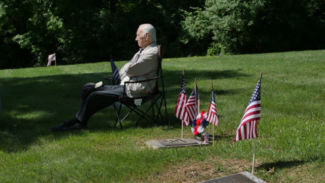 older man sitting among graves and flags listening to speakers during memorial day ceremonies at valhalla memory gardens may 29 2017 in bloomington... - veterans of foreign wars of the united states stock videos & royalty-free footage