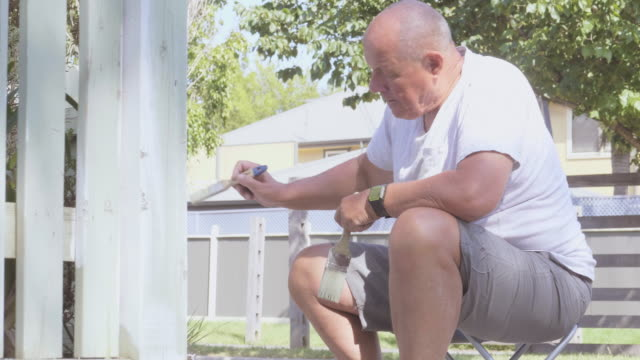 older man sitting down painting a garden fence - ワーキングシニア点の映像素材/bロール