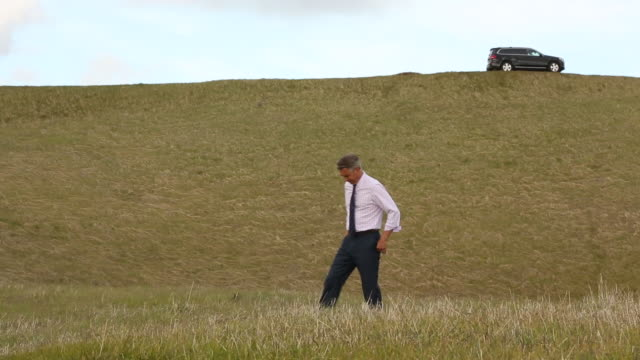 a older man walking in a open field with his vehicle behind him. - only mature men stock videos & royalty-free footage