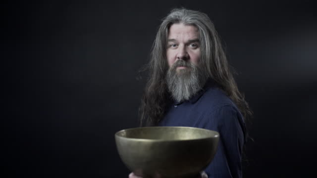 a older man with a tibetan singing bowl - 深皿点の映像素材/bロール