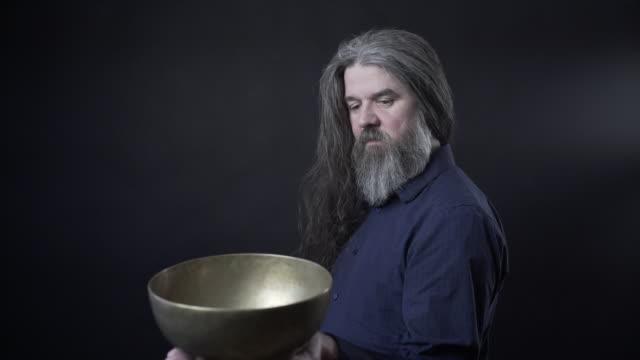 a older man with a tibetan singing bowl - 真鋳点の映像素材/bロール