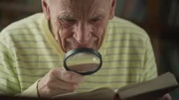 Older man with magnifying glass in hand looks to book page.