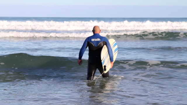 older man with surfboard under his arm walking in the ocean