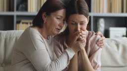 Older mature mom embrace console apologize upset young adult daughter