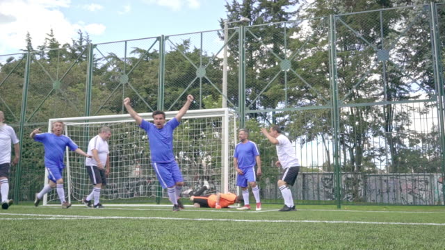 older men's soccer teams dressed in blue and white uniforms are in the middle of a game where one of the players charges a free kick and the others cover it - soccer goal stock videos & royalty-free footage