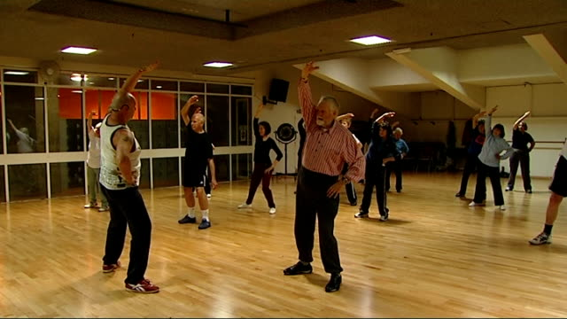 Older people taking part in Keep Fit class at YMCA centre Legs of elderly people doing exercises / Various of elderly people doing stretching...