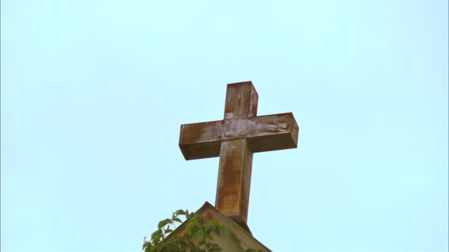 older, rusty looking cross at roof peak of vine covered building - imperfection stock videos & royalty-free footage