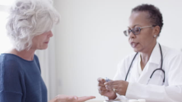 Older Senior Woman Having Medical Check-Up With Her Ethnic Female Doctor