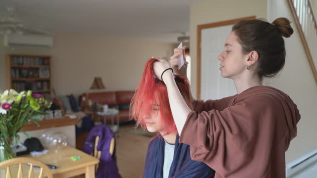 older sister cutting her younger sister's hair at home, and both of them having fun. - hairstyle stock videos & royalty-free footage