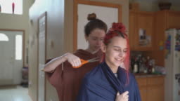 Older sister cutting her younger sister's hair at home, and both of them having fun.