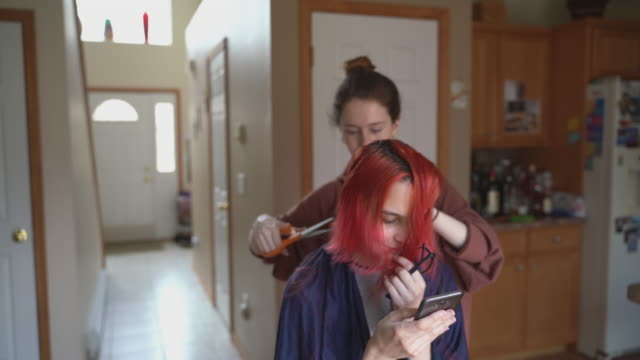 older sister cutting her younger sister's hair at home, while she is video chatting with her friends and streaming the process of the haircut online. - cutting hair stock videos & royalty-free footage