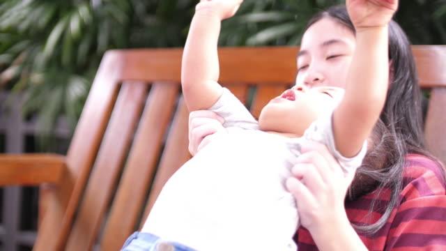vidéos et rushes de sœur aînée jouant avec son petit garçon - série d'émotions