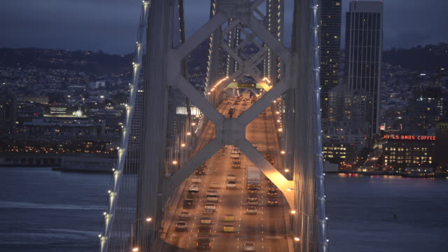 vidéos et rushes de older span of the oakland bay bridge at twilight as bridge lights come on. rush hour traffic pouring across the bridge both to & from oakland and san francisco. - rush hour