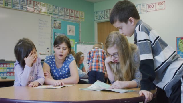 older students reading with younger elementary students - student leadership stock videos & royalty-free footage