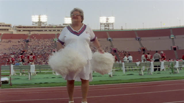 1985 ws older woman doing cheerleader routine at usfl game/ usa  - oggetto creato dall'uomo video stock e b–roll