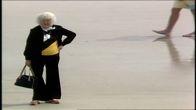 older woman in black and yellow outfit standing on beach in daytona florida - borsetta video stock e b–roll