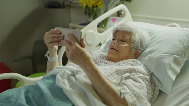 older woman in hospital bed video chatting with cell phone / salt lake city, utah, united states - adversity stock videos & royalty-free footage