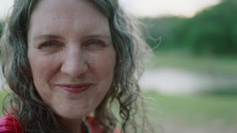 vídeos y material grabado en eventos de stock de cu slo mo. older woman laughs and smiles at camera by riverside. - mature women