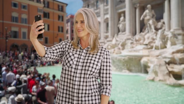 older woman takes a selfie at the trevi fountain in rome - monumento video stock e b–roll