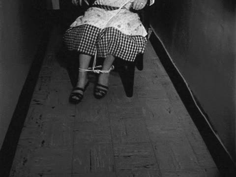 older woman wearing white apron and checkered dress bound and gagged in wooden chair placed cramped hallway woman struggles to free herself woman... - tied up stock videos & royalty-free footage