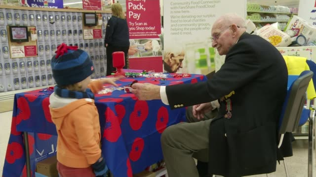 int young boy putting money into collection tin ron jones selling poppies at stall and giving to young boy ron jones interview sot i was a prisoner... - poppy stock videos & royalty-free footage