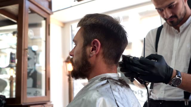 old-fashioned barber serving a customer at a hair salon - barber chair stock videos & royalty-free footage