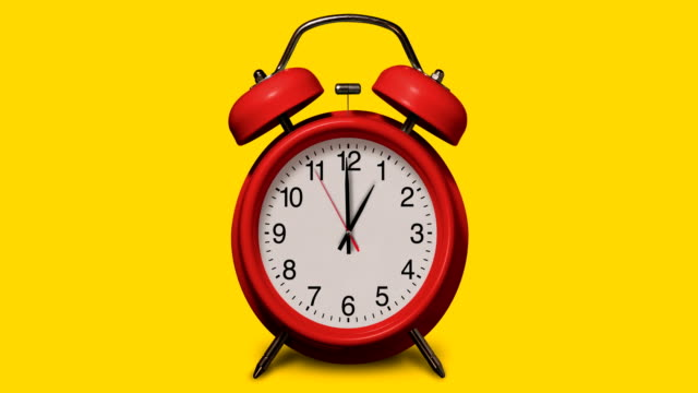 old-fashioned red alarm clock rings at 1 o'clock on yellow background - single object stock videos & royalty-free footage