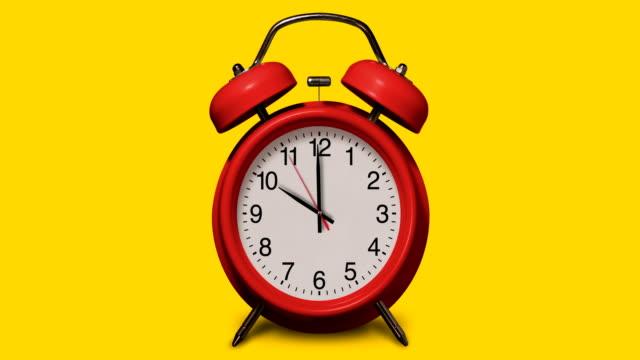 altmodischer roter wecker klingelt um 10 uhr auf gelbem hintergrund - 10 seconds or greater stock-videos und b-roll-filmmaterial