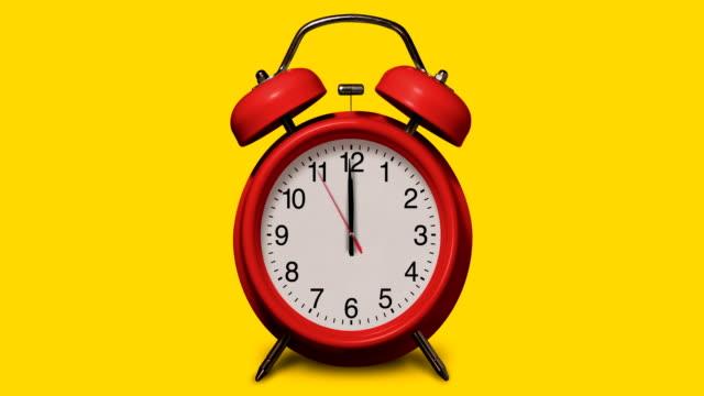 altmodischer roter wecker klingelt um 12 uhr auf gelbem hintergrund - 10 seconds or greater stock-videos und b-roll-filmmaterial