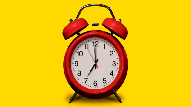 old-fashioned red alarm clock rings at 7 o'clock on yellow background - school bell stock videos & royalty-free footage
