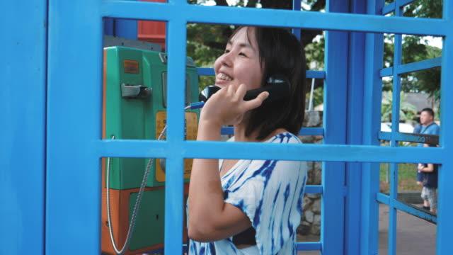 stockvideo's en b-roll-footage met ouderwetse telefoongesprek, typische blauwe telefooncel - telefooncel