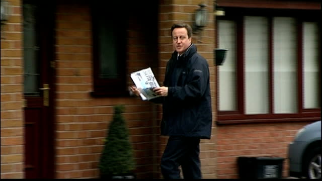 vídeos y material grabado en eventos de stock de david cameron campaigns england greater manchester oldham ext david cameron mp along and posting campaign leaflet through letterbox cameron towards... - formato buzón