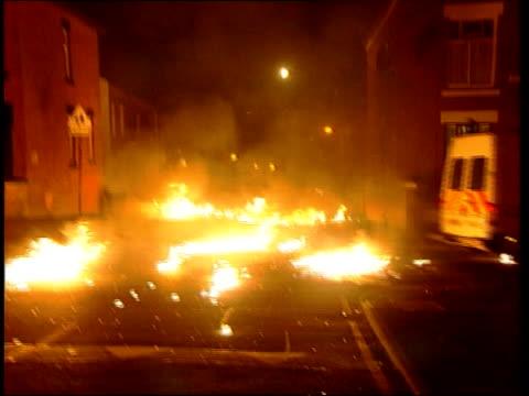 Aftermath ITN ENGLAND Lancashire Oldham Burntout fridge on pavement PULL OUT burnt debris scattered across road in f/g GV Debris across road NIGHT LA...