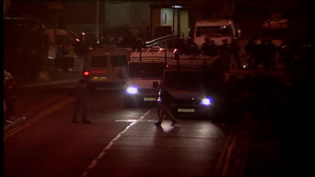 Greater Manchester Oldham EXT Bend in road as white youths stand around on side of road / police vans parked in residential area as riot police stand...